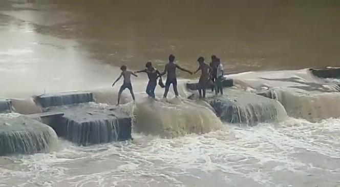 चेन बनाकर आधा दर्जन बच्चों ने पार की उफनती नदी, बैराज स्टॉप डेम के तेज बहाव में फंसे थे