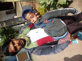 अपाहिज बेटे को गोद में उठाकर, सात साल से दफ्तरों के चक्कर काट रहा पिता